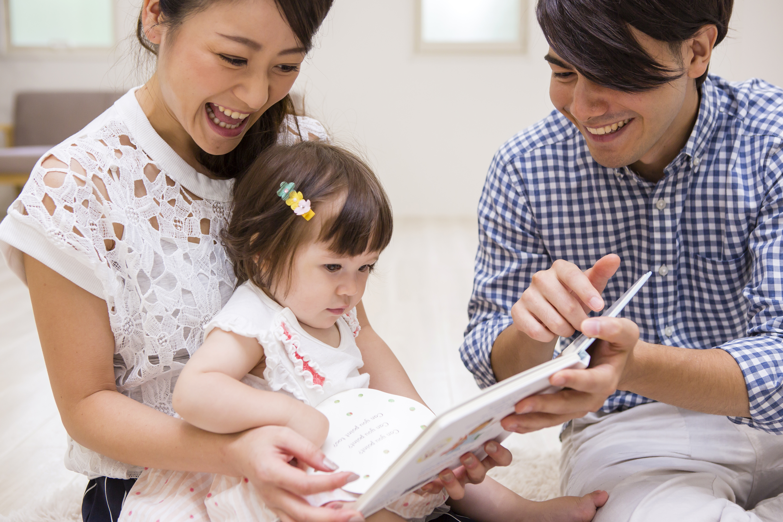 子供に絵本を読む家族